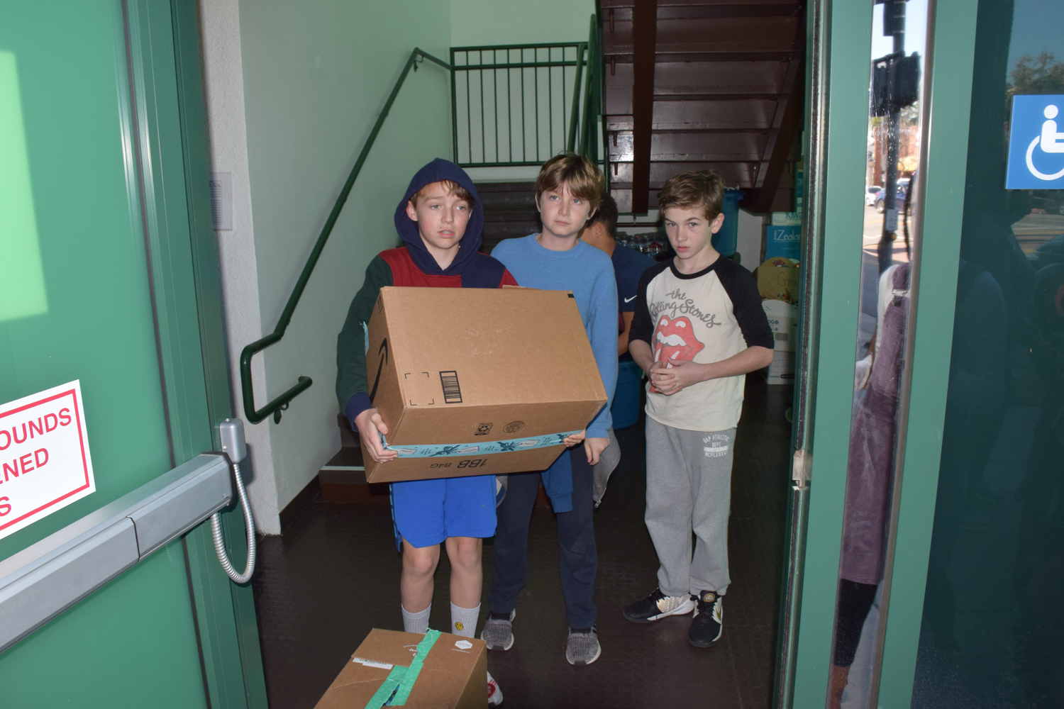5th graders help load the MEND truck with boxes and bags of gently-used clothing donations.