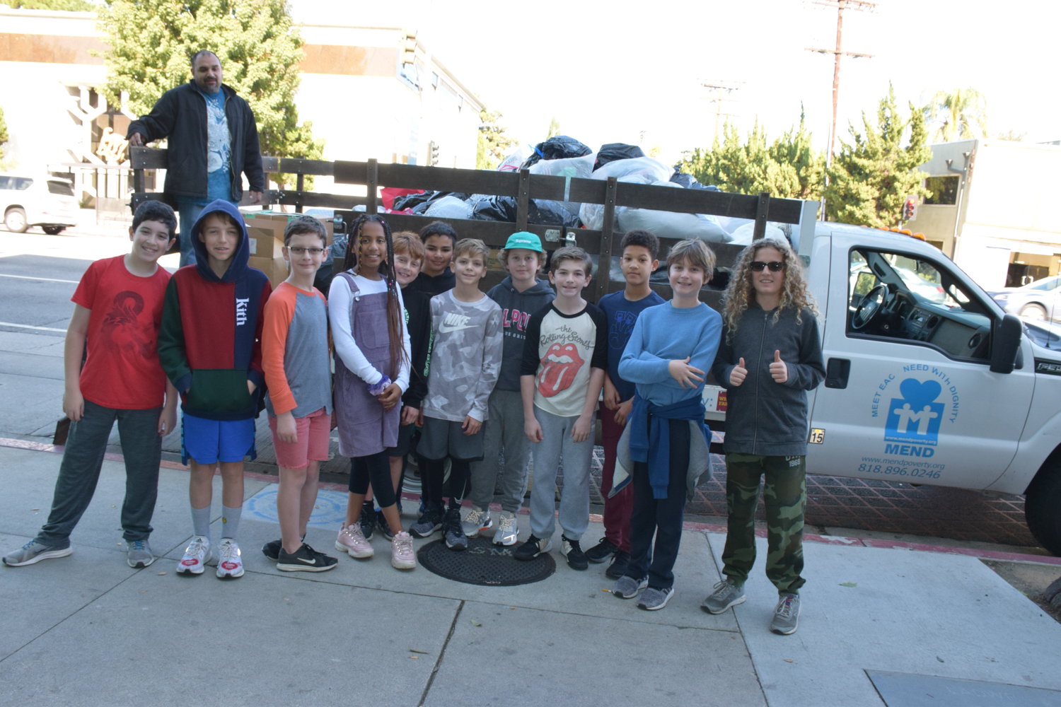 5th graders pose after helping to load the MEND truck.