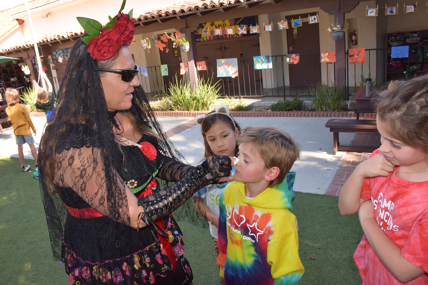 Parent artists paint faces for Day of the Dead.